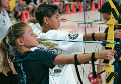 New Mexico Game & Fish educator oversees youth during archery practice.