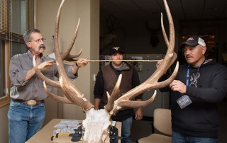 Hunter Joseph Jaramillo (right) with son Jared (center) assist official Boone and Crockett Club Measurer Eric M. Rominger, PhD, Bighorn Sheep Biologist NMDGF.