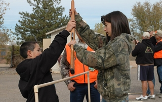 Students learning to safely cross a fence during a Hunter Education Course from New Mexico Department of Game and Fish.