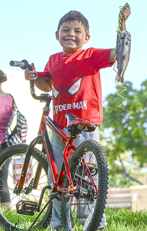 Survey indicates fishing even better in New Mexico (boy with fish and a bike)
