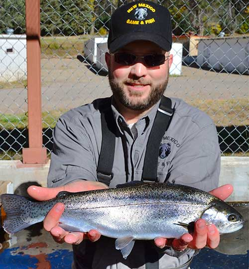 Scott Bernard, manager, shows off a large rainbow trout raised at the New Mexico Department of Game and Fish Lisboa Springs Fish Hatchery.